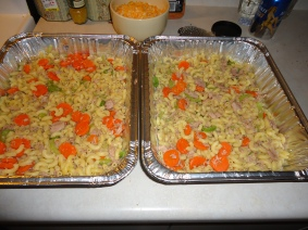 Elbow macaroni, cooked al dente, chopped carrots and celery, canned tuna, mushroom soup, foil casserole dishes (with lids), grated cheese.